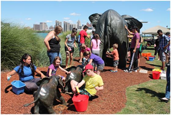 Photo of group washing elephant sculpture