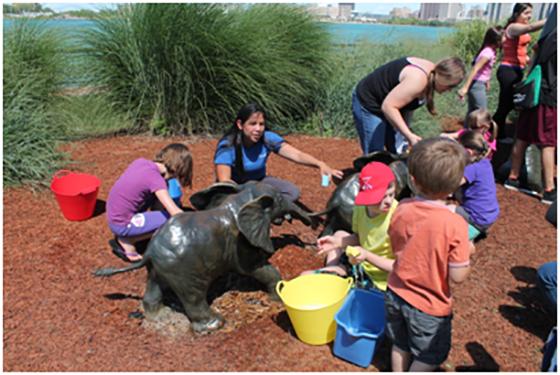 Photo of group washing baby elephant sculpture
