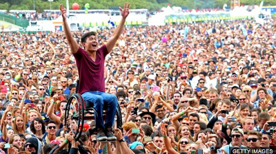 disabled man enjoying music event lifted by crowd in wheelchair