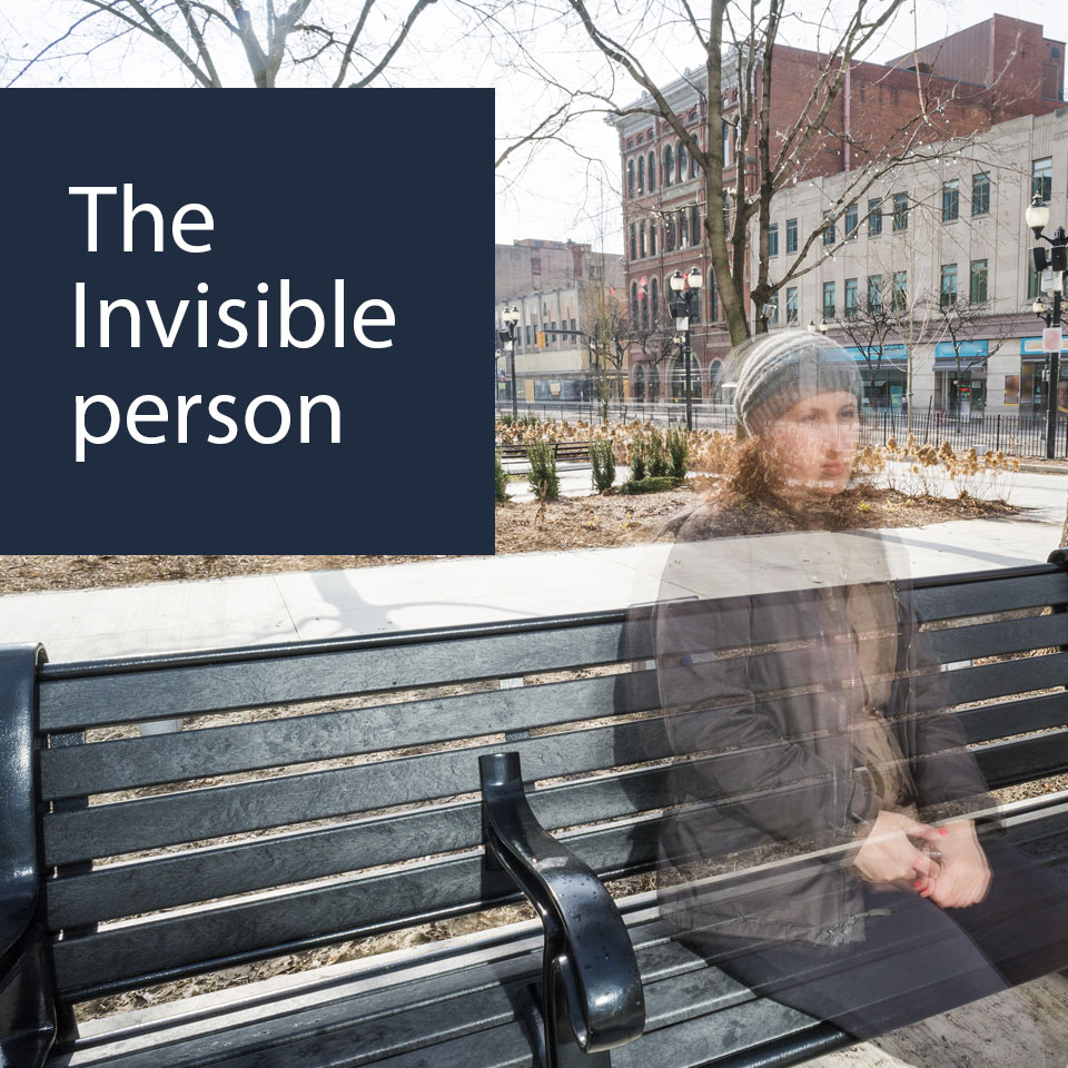 Woman sitting on a bench seems to be transparent depicting being invisible