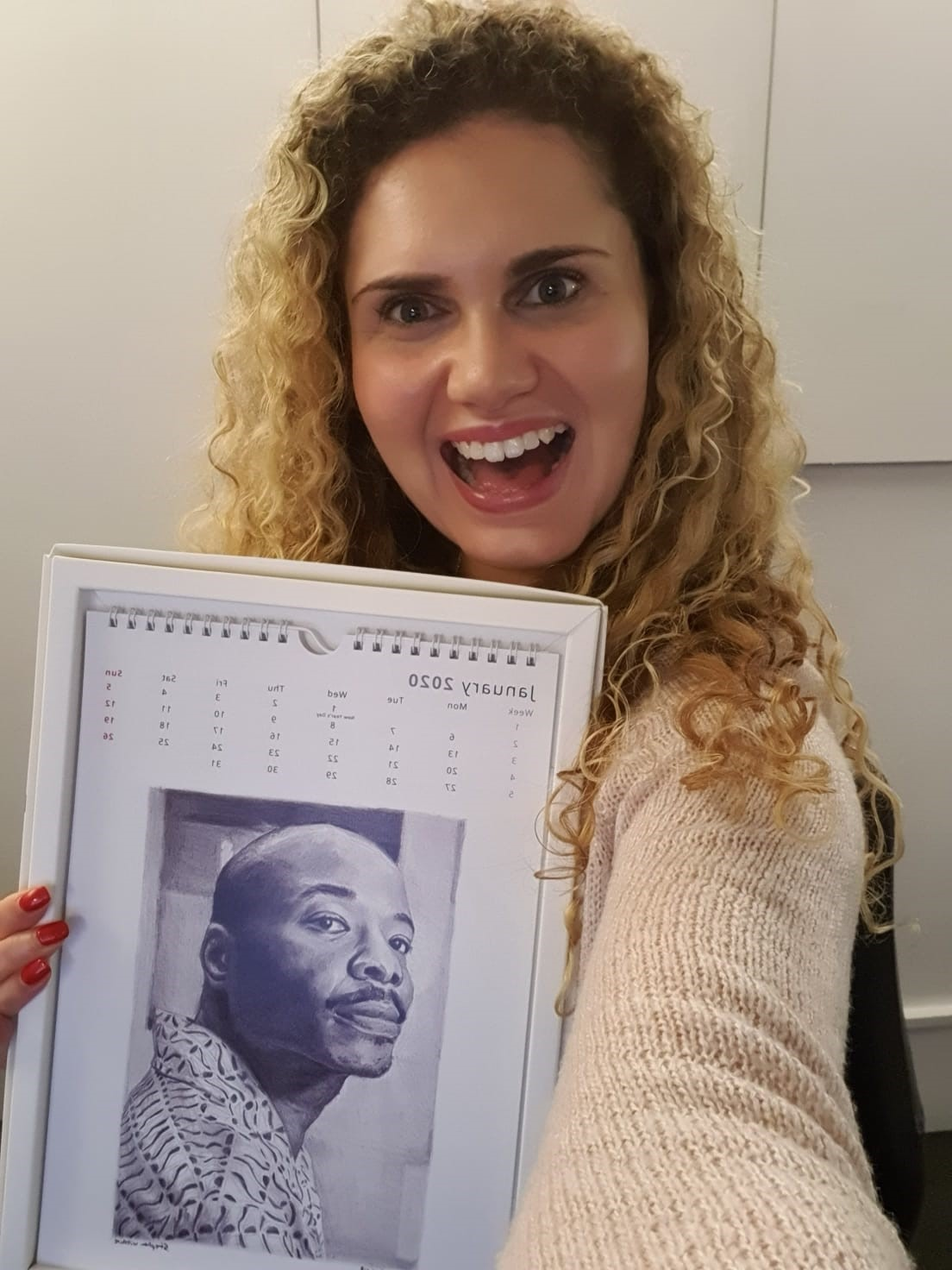 Rachael holds up the new Stephen Wiltshire calendar for the Snap office