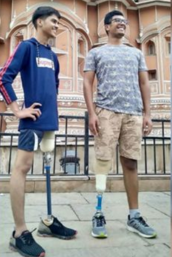 Two young men happily show their prosthetic legs with sockets made from recycled bottles