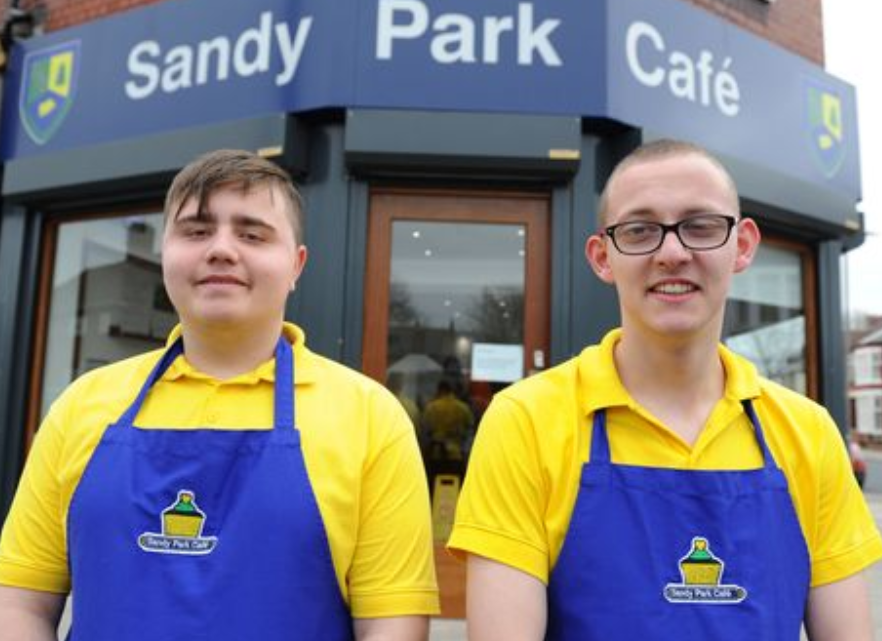 Two students stand in front of the Sandy Park Cafe