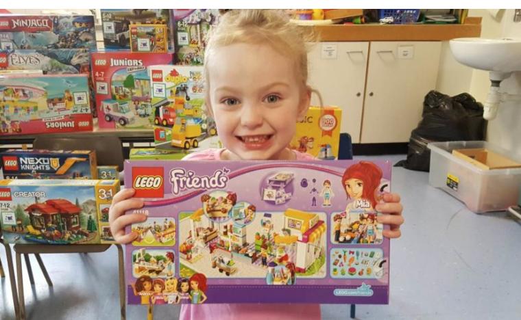 Little girl holding LEGO box