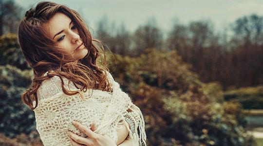 Dromerige jonge vrouw met omslagdoek