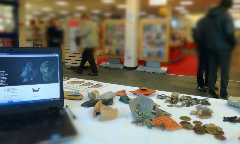 laptop and archaeological objects on table