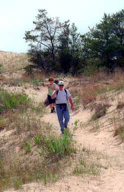 Hikers in the open dunes at Ludington State Park.