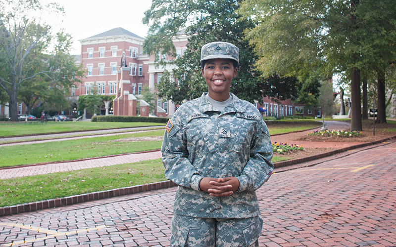 Female student dressed in military uniform standing on brick streets of campus with Main Quad and Main Hall in the background.