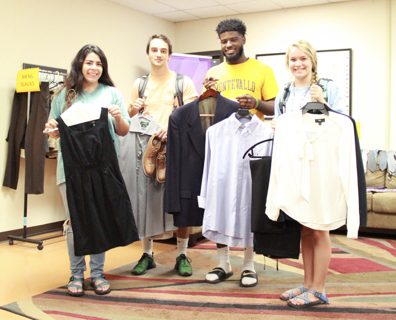 Students holding professional clothing at the Dress for Success event.