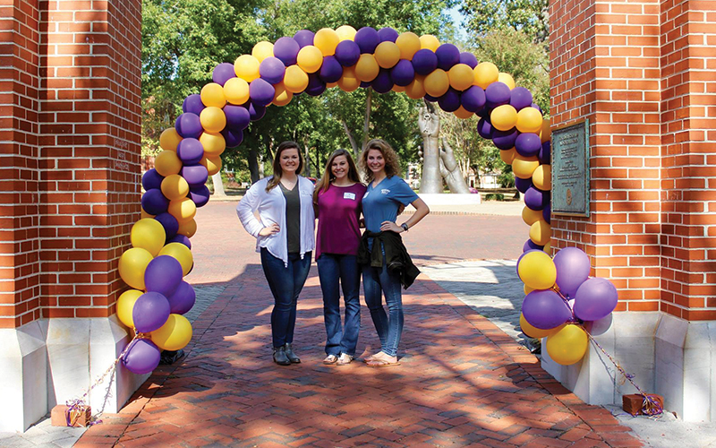 Potential students standing under balloon arch at Bowers Colonade