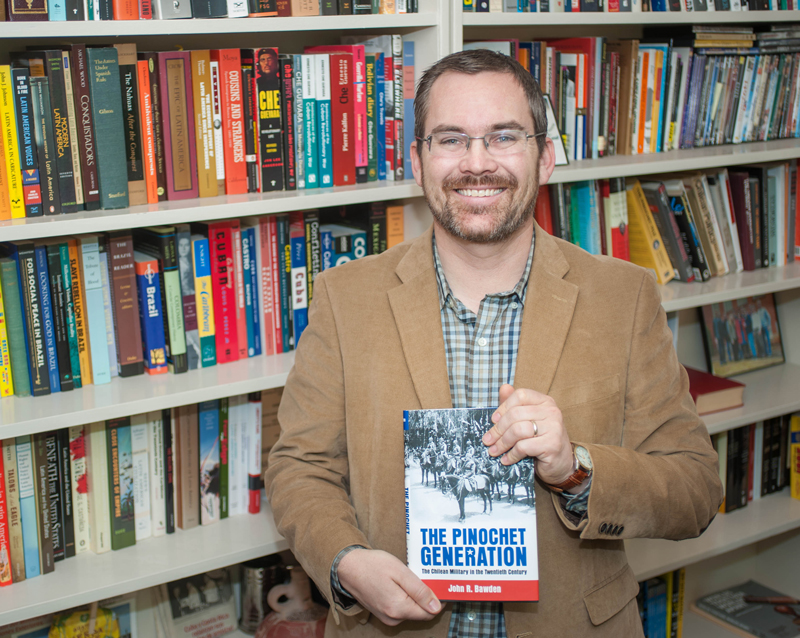 John Bawden holding The Pinochet Generation, the book he authored, standing in front of shelves filled with history books.
