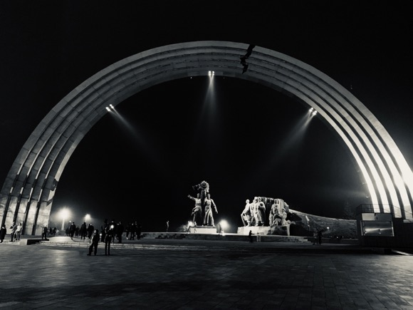 The People's Friendship Arch in Kyiv, Ukraine. Under the arch are two figures, a Ukrainian and Russian worker standing together. Note the crack that has been painted on the arch.