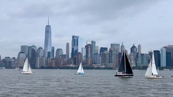 View of Manhattan skyline from Ellis Island with sailboats going by.