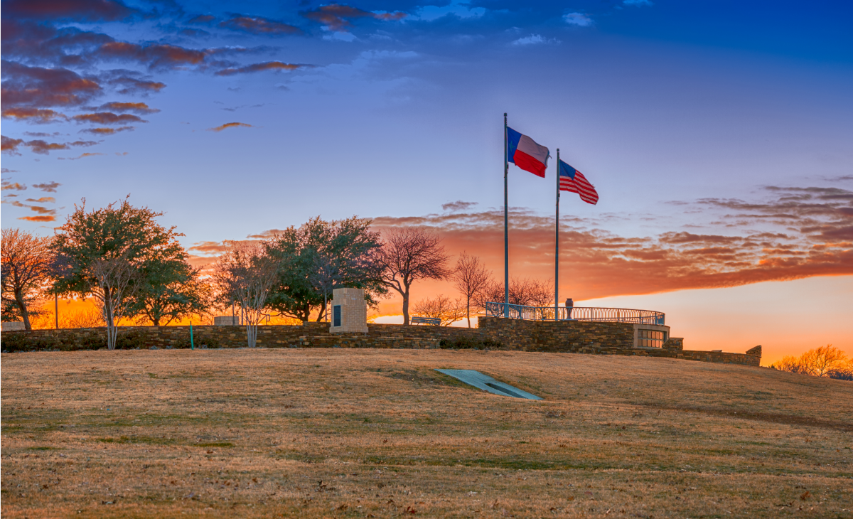 Texas and American flags fly over a brick walkway at Frisco Commons Park in Frisco, Texas, at sunset. The sky is blue and orange with sparse clouds