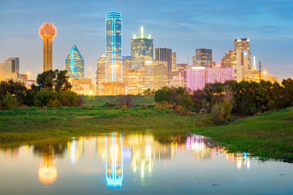 Dallas skyline at dusk above a body of water