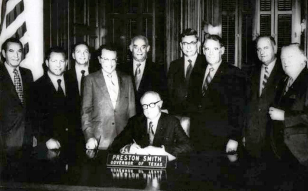 Texas Gov. Preston Smith signing legislation with Real Estate Center supporters behind him. 1971