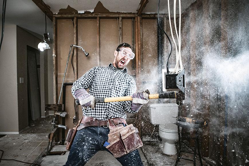 Man enthusiastically demolishing bathroom
