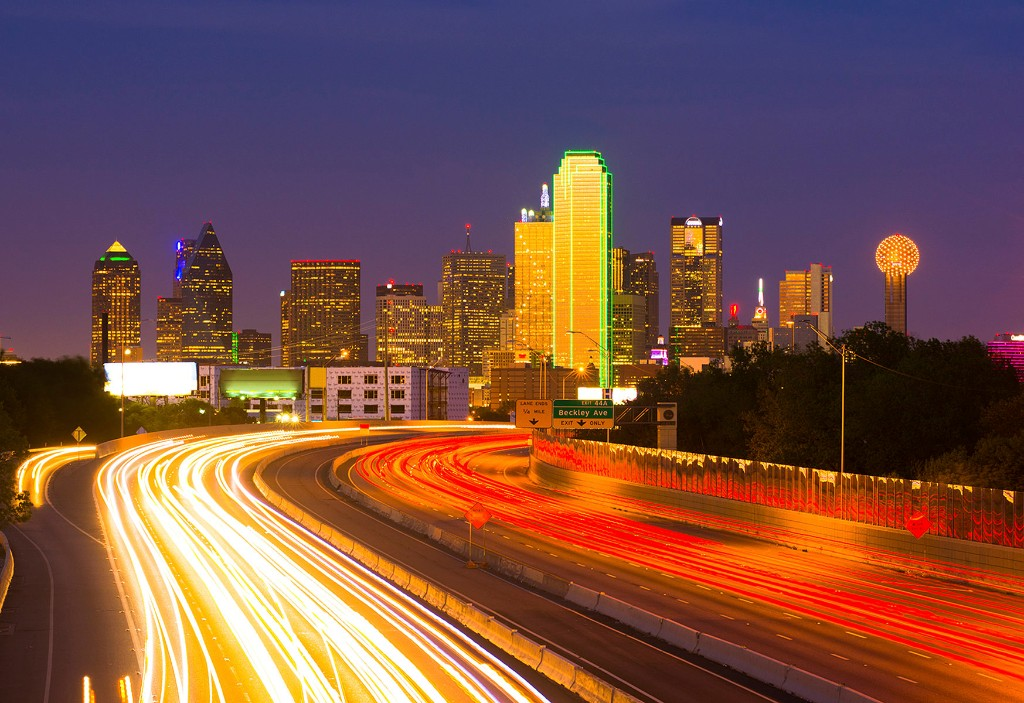 Dallas skyline at night with cars driving on highway with long exposure