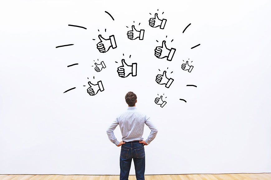 Man staring at a wall with thumbs up symbols drawn on it