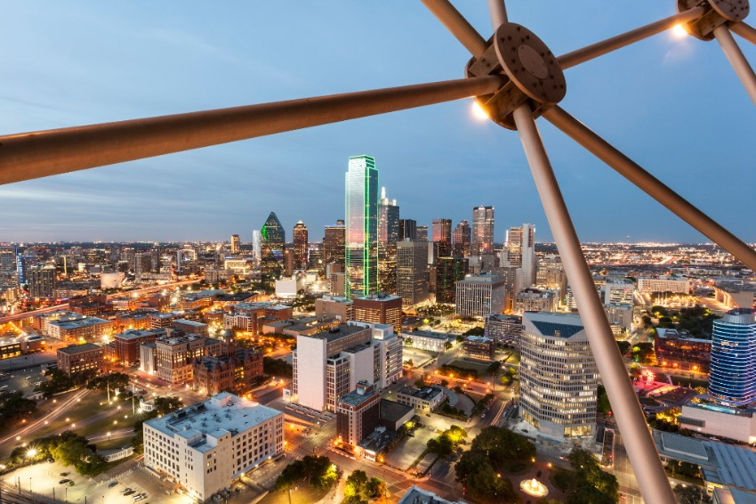 A view of the Dallas skyline at dusk from a bridge.
