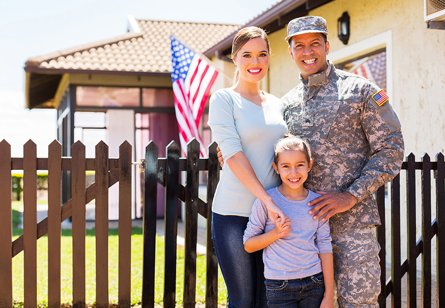 Mixed-race military family standing outside of home