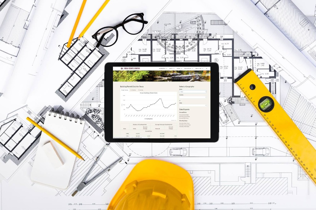 Building permit data on an iPad over blueprints