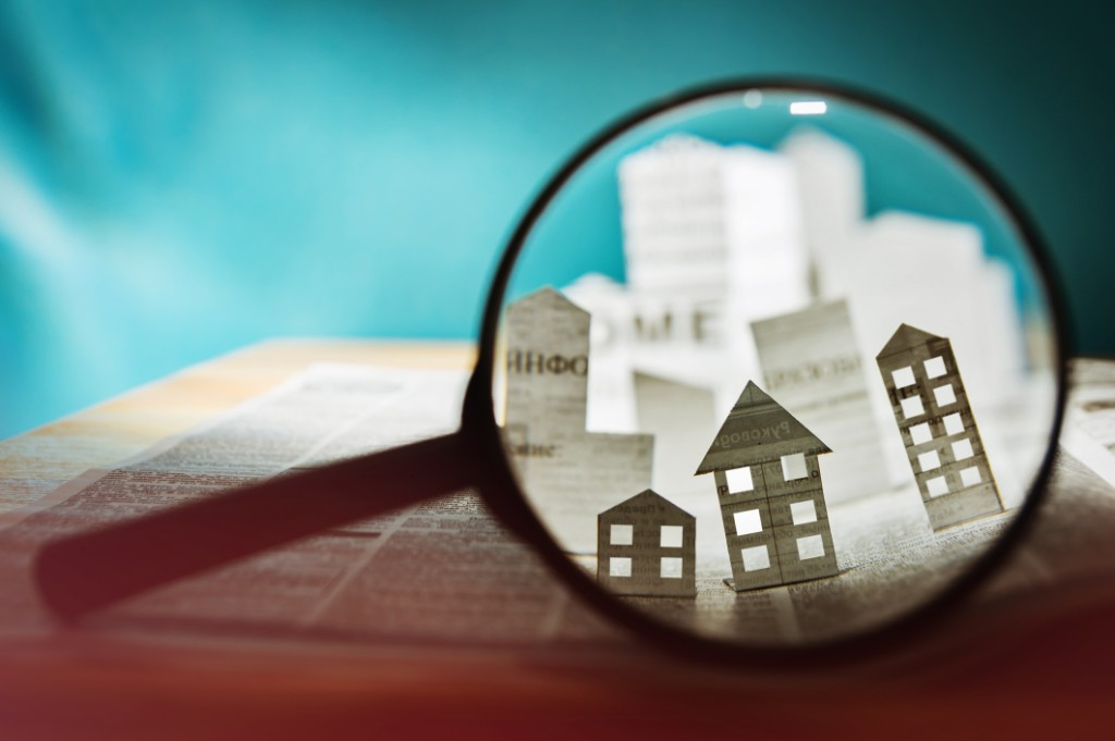 A magnifying glass focuses on houses made out of newspaper