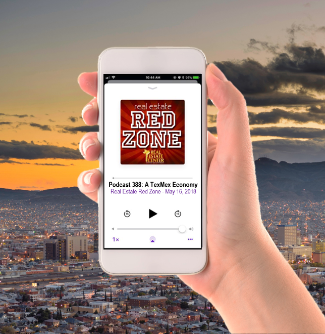 A woman holds a phone with the Red Zone podcast on it in front of the El Paso skyline.