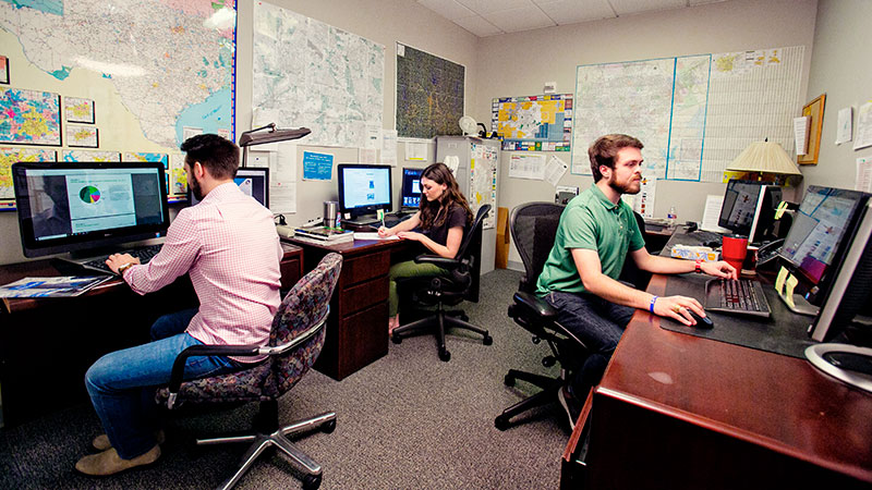 Three student workers working in their office