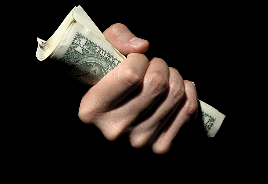A hand holds a fistful of US dollar bills