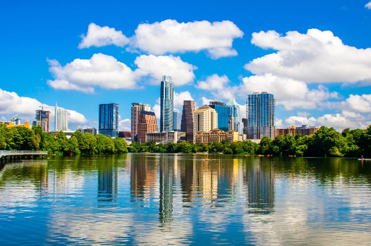 The Houston skyline on a bright, sunny day. The blue sky, tall buildings, and green trees are reflected in cool waters.