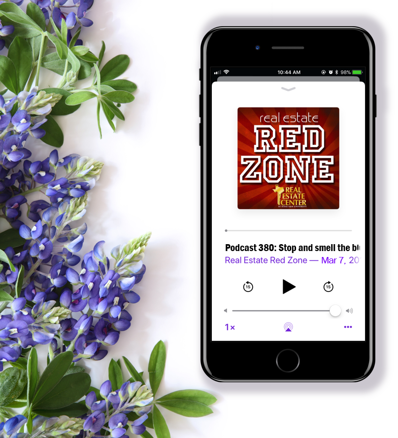 Real Estate Red Zone podcast plays on an iPhone near a bouquet of bluebonnets.