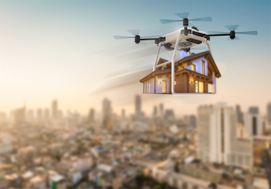 A drone carries a small house through the city.