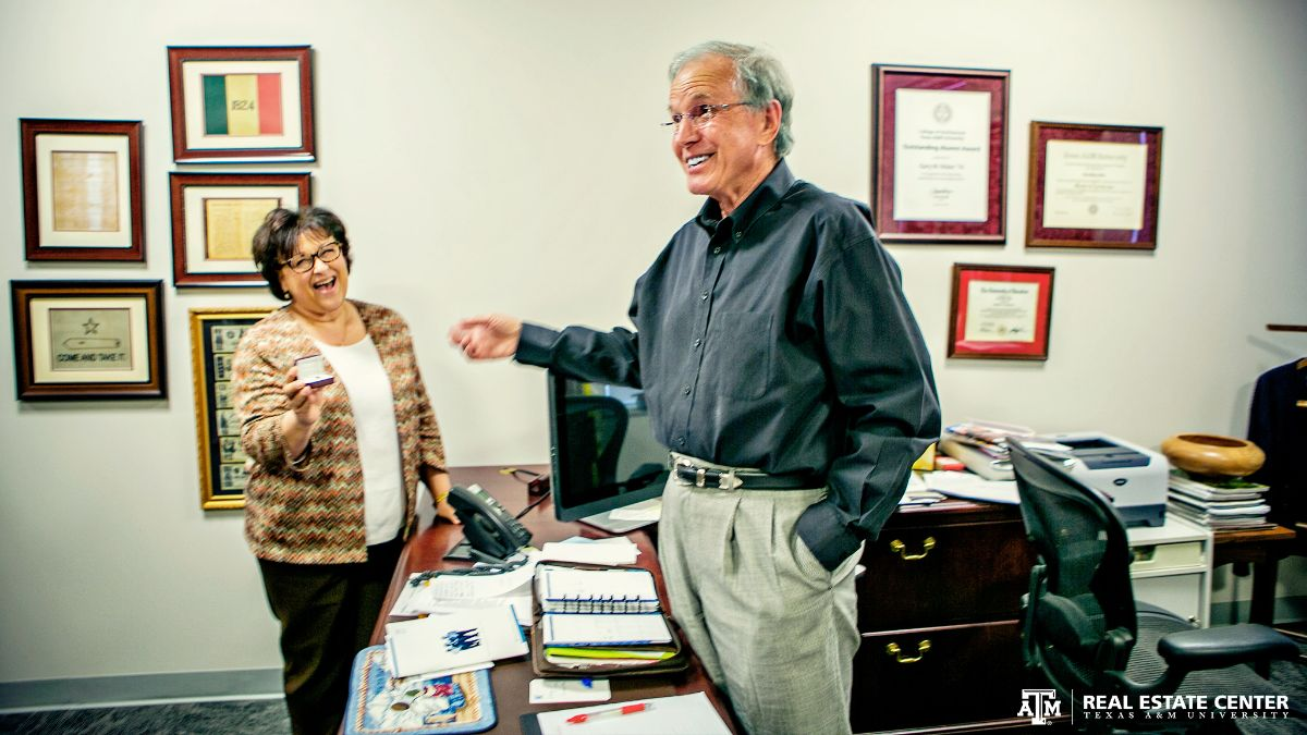 Real Estate Center Business Coordinator Pamela Canon presents Director Gary Maler with a commemorative pin in honor of his 40 years of service at Texas A&M University.