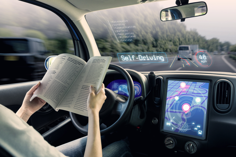 Woman reading in self-driving vehicle.