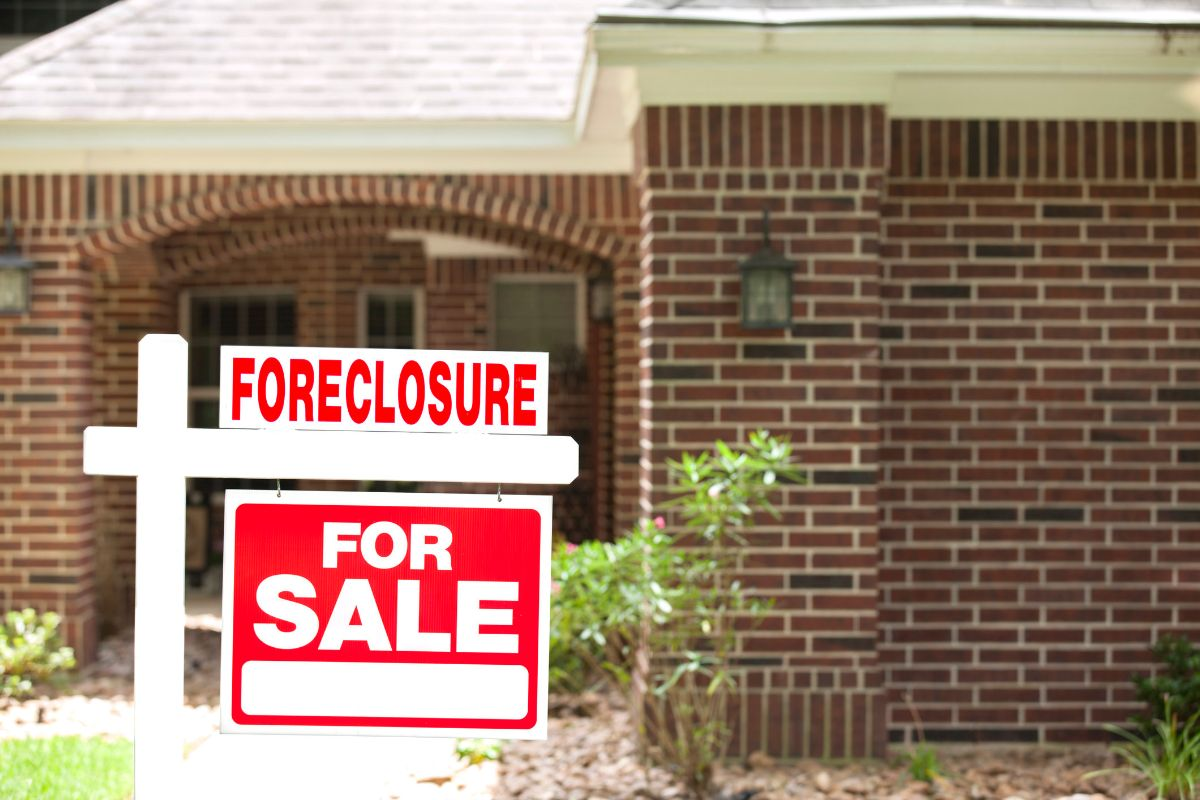 Foreclosure sign in front of brick house