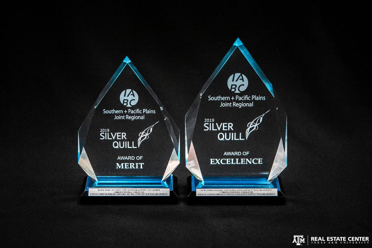 Two clear glass awards with a bluish tint that read