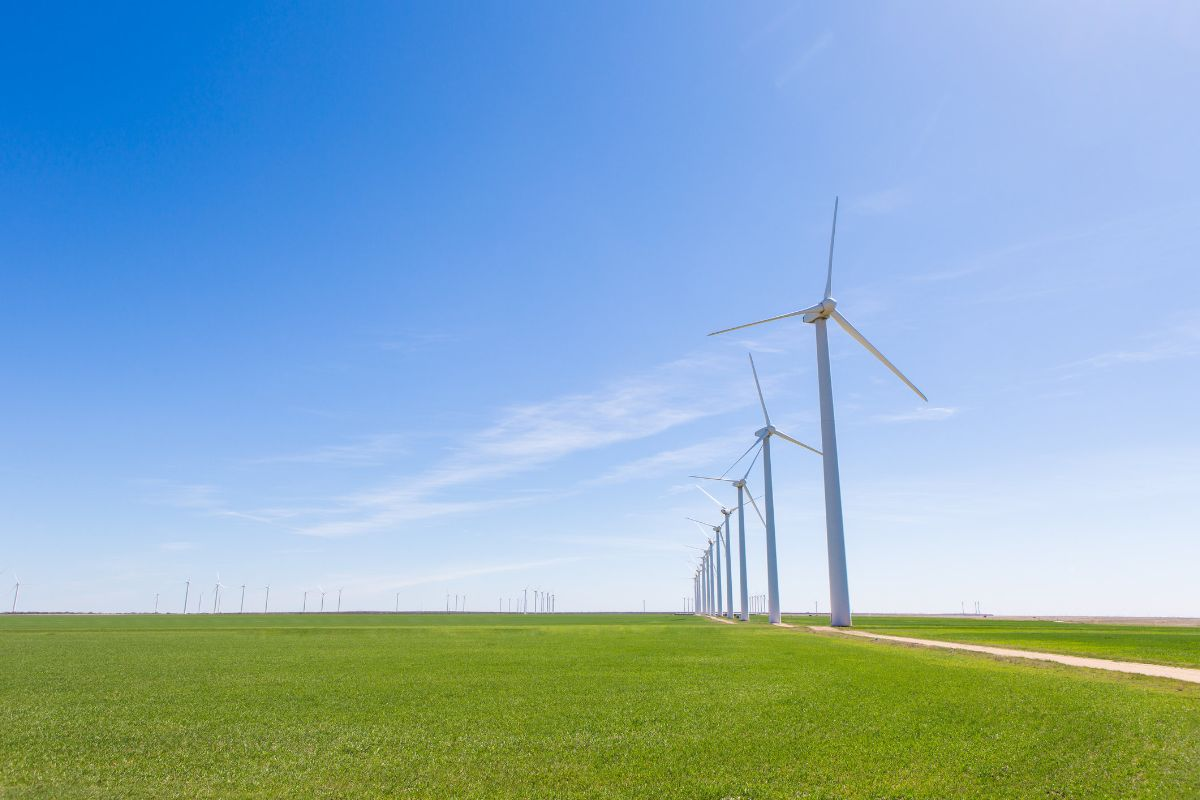 Windmills on flat green ground behind a bright blue sky. Via Getty Images