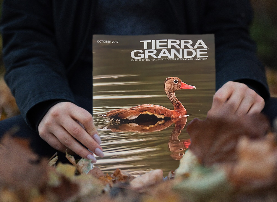 Woman holding October's issue of Tierra Grande magazine.