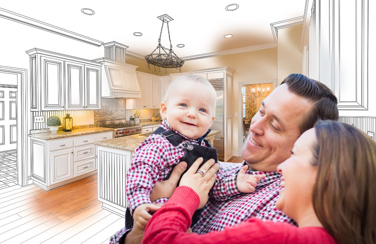 Man and woman holding a baby in front of a kitchen remodel