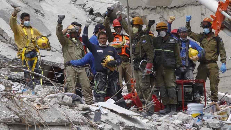 Varias personas de los cuerpos de ayuda trabajando en los escombros del terremoto.