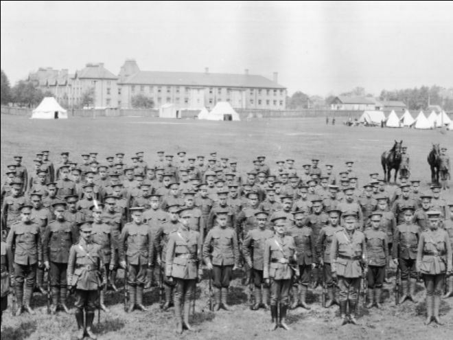 A crowd of WWI soldiers stand to attention on a field. Black and white