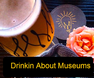 Glass of beer on coaster, caption reads 'Drinkin About Museums'