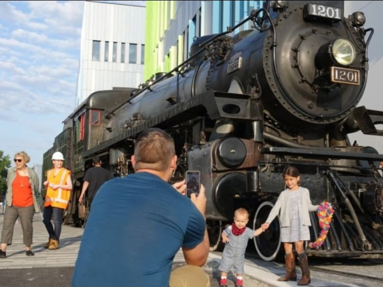 Man takes picture of children in front of steam engine