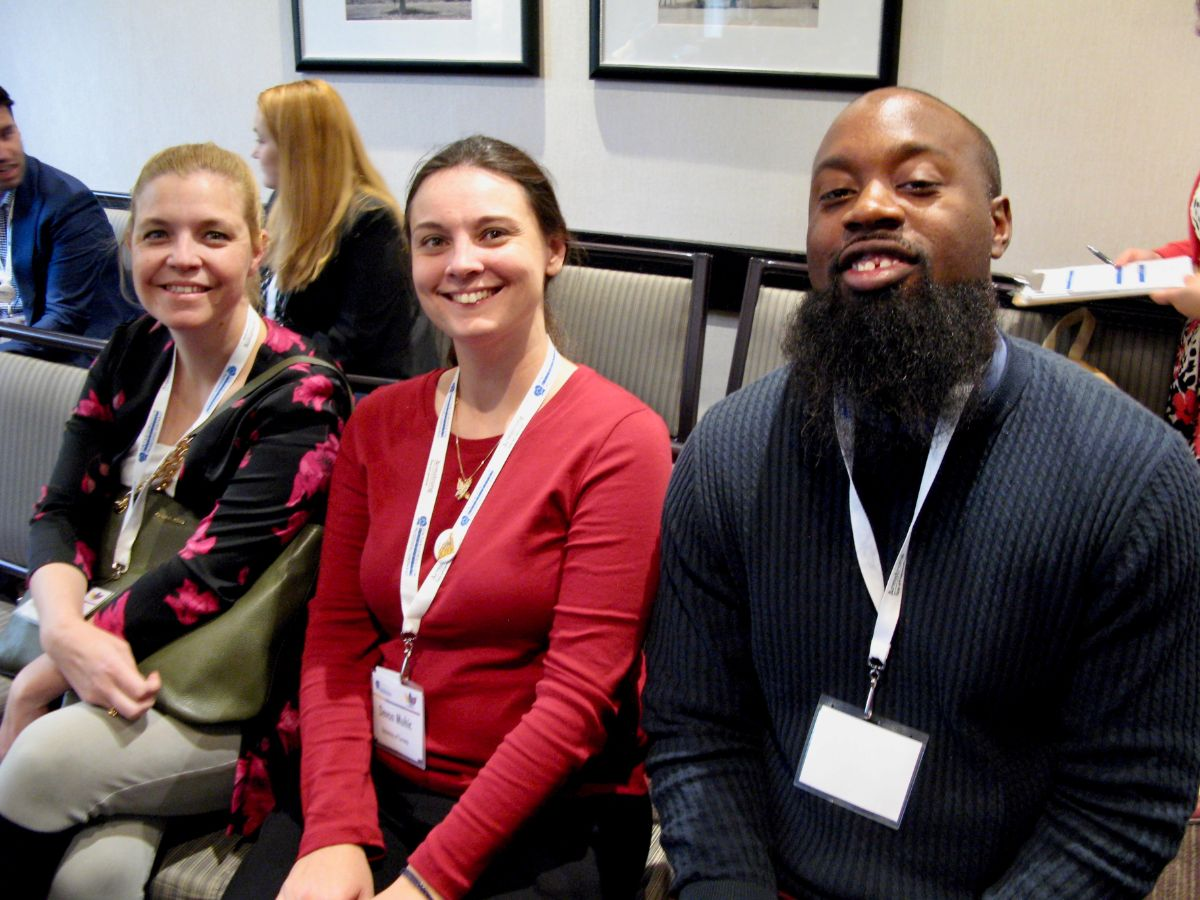 Three conference attendees smile at the camera