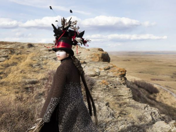 Woman standing on bluff wearing large black hat