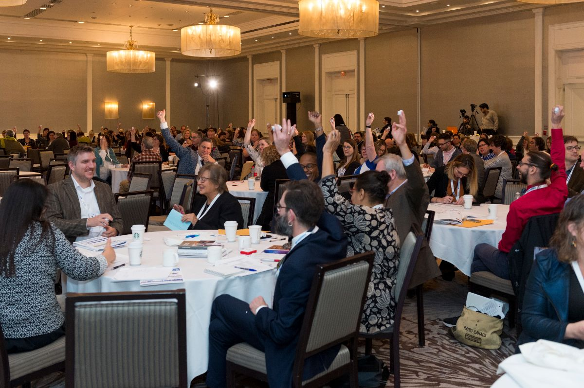 OMA conference guests sitting around tables in a large ballroom raise their hands