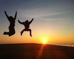 Silhouettes of people jumping against a sunset