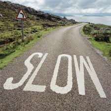 Picture of road with the word slow written on the road.