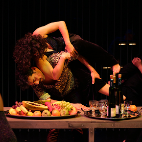Male and female dancer in front of a table of food